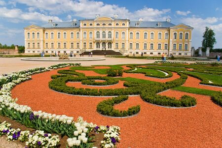 Yellow baroque palace with garden in foreground