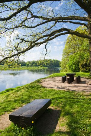 Wooden table and benches at river and tree photo