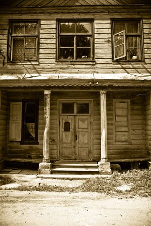 Facade with windows of old wooden house. Sepia photo