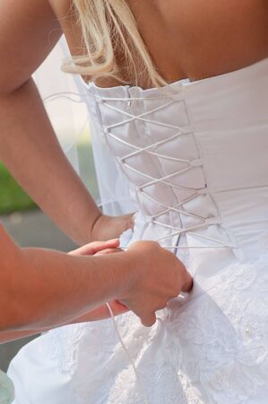 Assistant girl tightening brides white corset. Vertical shot Stock Photo - 7619631