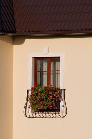 Close-up of french balcony with window-box full of flowers photo