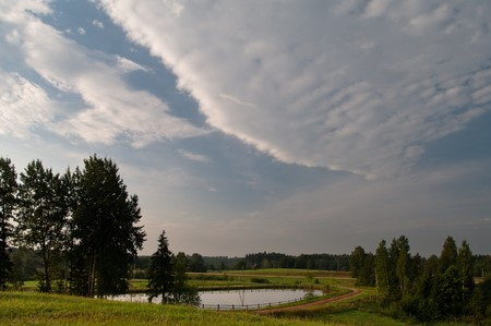 Cloudscape in blue morning sky over pond photo