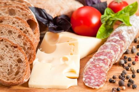 Italian bread ciabatta, salami, cheese, tomato and basil. Focus on foreground photo