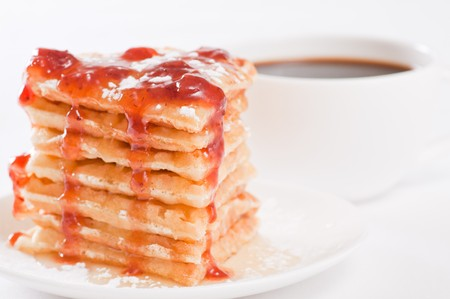 Pile of waffles with honey, strawberry jam and powdered sugar and coffee on white background photo