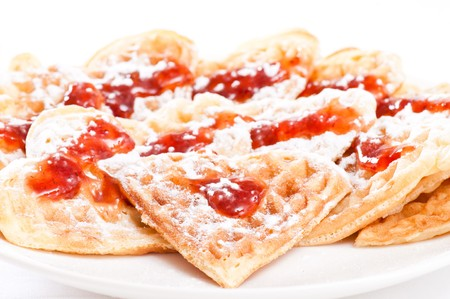 Stack of waffles in shape of heart with strawberry jam and powdered sugar on plate photo