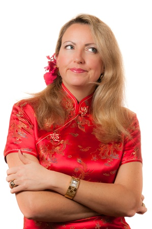 Beautiful thoughtful blond caucasian woman in red chinese dress cheongsam with crossed hands and flower in hair photo