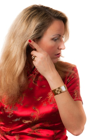 Beautiful blond caucasian woman in red chinese dress cheongsam with serious face expression folding back hair photo
