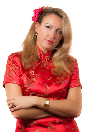 Beautiful blond caucasian woman in red chinese dress cheongsam with crossed hands and boring face expression photo