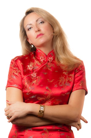 Beautiful blond caucasian woman in red chinese dress cheongsam with crossed hands and arrogant face expression photo