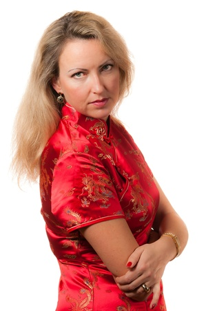 Beautiful blond caucasian woman in red chinese dress cheongsam with crossed hands directly looking in camera photo