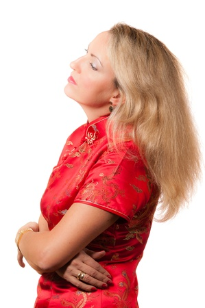 Beautiful blond caucasian woman in red chinese dress cheongsam with crossed hands and sad face expression looking to the side photo