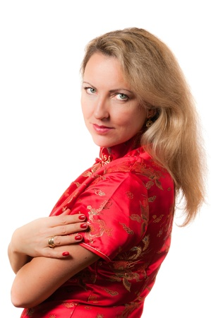 Beautiful blond caucasian woman in red chinese dress cheongsam with crossed hands smiling and directly looking in camera photo