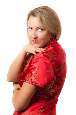 Beautiful blond caucasian woman in red chinese dress cheongsam with saucy smile directly looking in camera photo