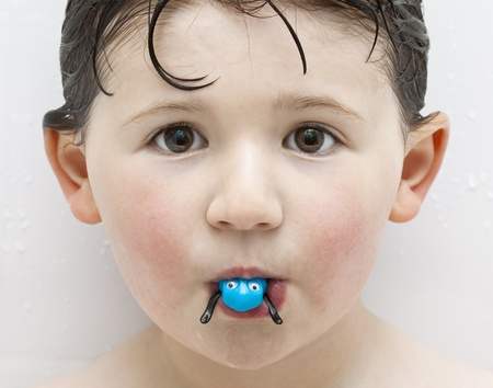 Boy in Tub Playing with Blue Plastic Toy Frog photo