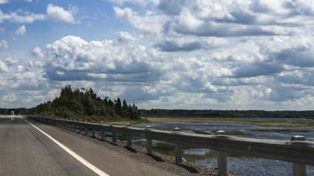 Highway, Pond, Trees and Cloudy Blue Sky in Eastern Newfoundland, Canada photo