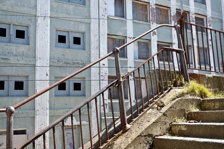 urban decay: A Crumbling Stairway with Rusty Railing:  An image in an urban setting highlighting damaged steps and rusted iron railing in the foreground.  In the background is the facade of an old concrete building showing decay with boarded windows.