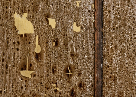 Closeup of old wooden floorboards with highly textured grain and peeling yellow and brown paint