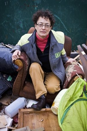 squatter: Woman Sitting on Broken Chair in Dumpster   A middle aged woman with glasses sitting in a broken chair surrounded by other refuse  Stock Photo