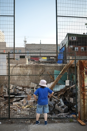 gentrification: Boy Looking at Demolition Site Through Fence    A boy in shorts and summer hat stands on a sidewalk looking through a chain link fence at an urban demolition site   The boy s back in turned to the camera