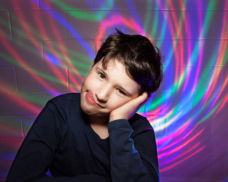 Fun Portrait of Boy Sticking his Tongue Out with Colourful Background Stock Photo