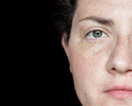 Closeup Portrait of Woman with Freckles and Green Eyes Isolated on a Black Background