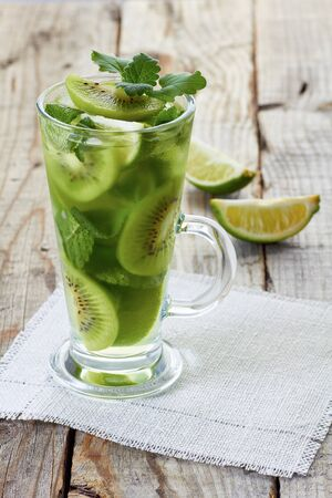 textil: Glass of fresh fruit lemonade with kiwi, lime and mint. On wooden table with white textil napkin.