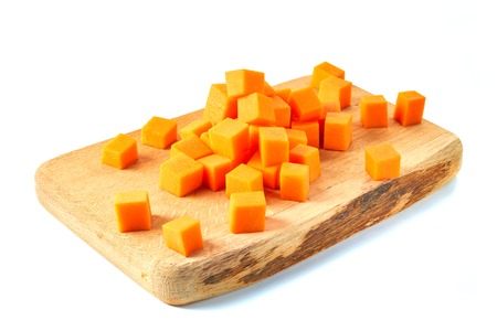Sliced pumpkin cubes on wooden board. Isolated on white background. Stock Photo