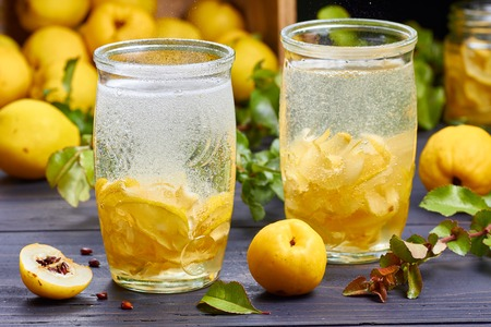 carbonated drink with syrup of japanese quince on fresh quince fruits background over dark wooden table Stock Photo