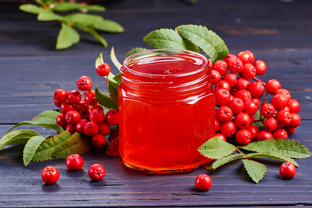 Glass jar of syrup of rowan berries and  fresh berries and leaves on dark wooden table.
