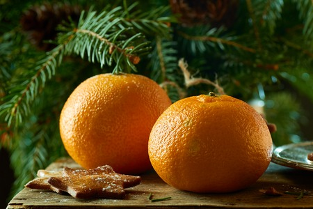 Tangerines and ginger cookies on spruce branches background. Christmas and new year concept. Stock Photo