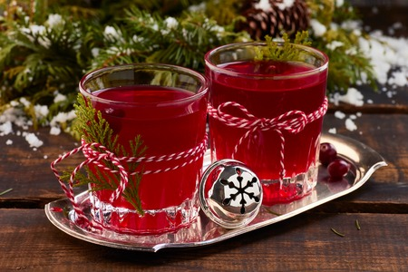 Two glases of cranberry fruit drink on old wooden table. Christmas concept.