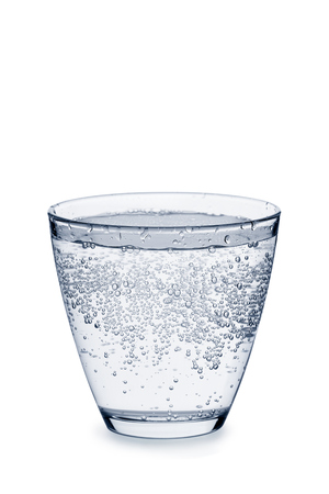 Glass of carbonated water with bubbles on white