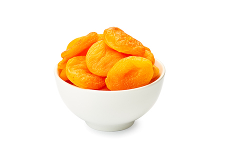 Bowl of dried apricots on white Stock Photo