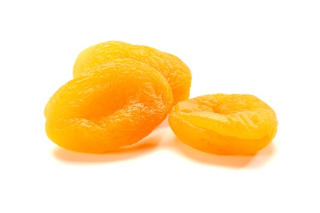 Three dried apricots on white Stock Photo