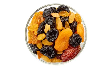 Glass bowl of dried fruits mix on white Standard-Bild