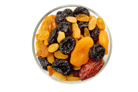Glass bowl of dried fruits mix on white Foto de archivo