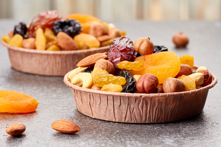 Paper forms with mix of dried fruits and nuts over stone background Stock Photo
