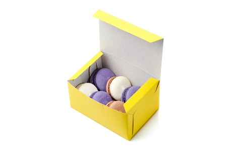 Yellow packing box with colorful macaroons on white