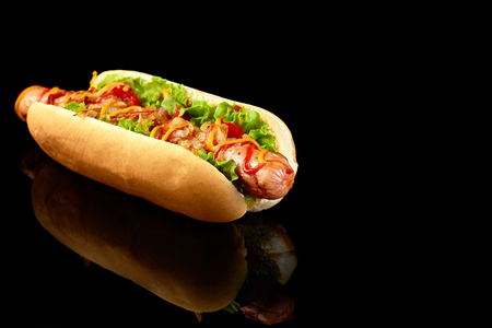 Tasty hot dog with reflection on black background