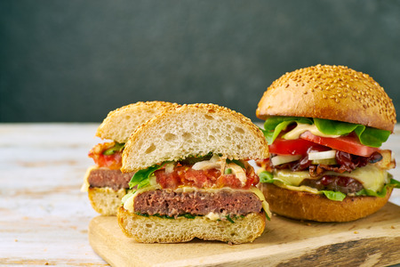 Whole and divided hamburger on old wooden table