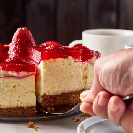 Hand lifted up piece of cheesecake with strawberries