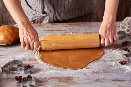 Woman hands rolling up gingerbread dough on table
