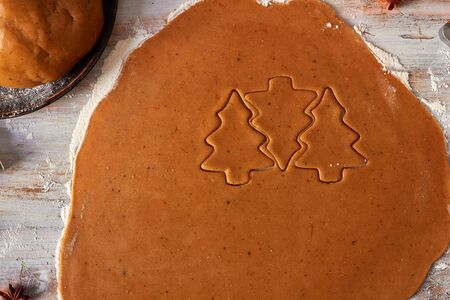 Raw gingerbread cookies shapes on wooden table
