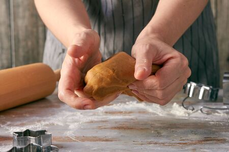 Womans hands mash gingerbread dough on the table