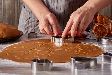 Womans hands make gingerbread cookies shapes on table