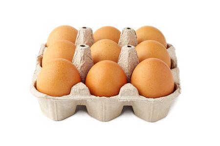 Brown fresh eggs in retail tray on white