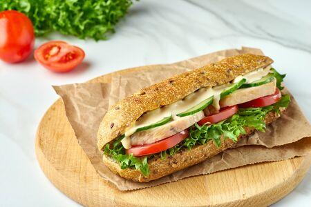 Duża kanapka z kurczakiem i warzywami na drewnianej desce