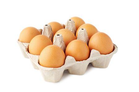 Nine brown fresh eggs in retail tray on white