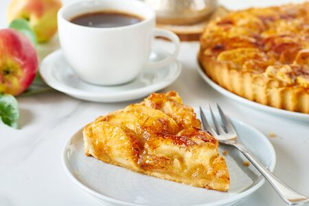 Piece of homemade french apple tart on dish and coffee