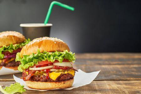 Zwei Hamburger und eine Tasse Getränk auf dunklem Holztisch serviert
